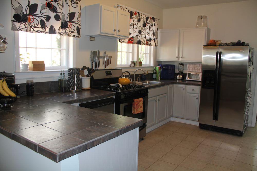 white cabinets kitchen design with dark gray tile countertops