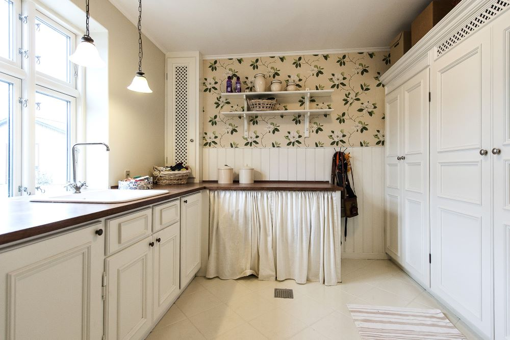 small kitchen with a beautiful wall paper decoration and cherry wood countertops