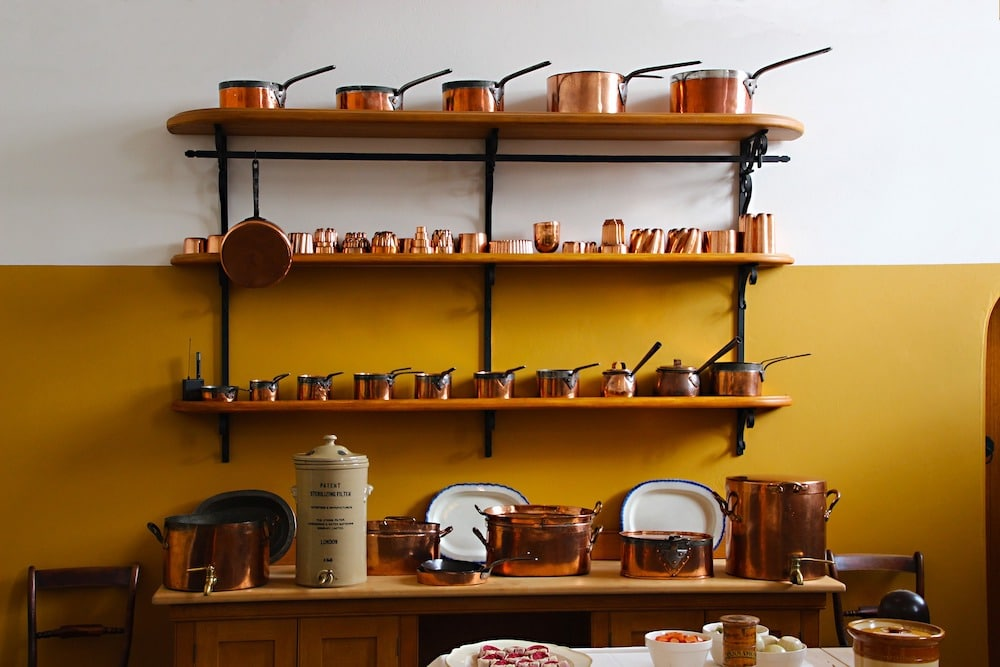 set of copper kitchen pots displayed on wooden open shelves