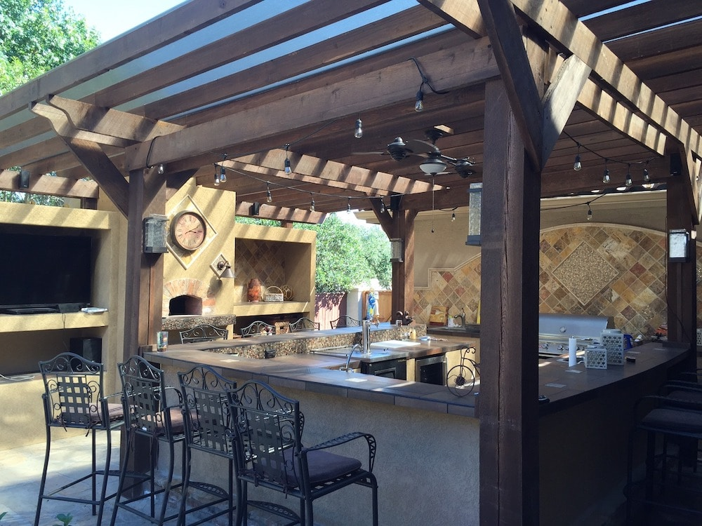 beautiful outdoor kitchen with ceramic tile countertop cover with a see-trough ceiling
