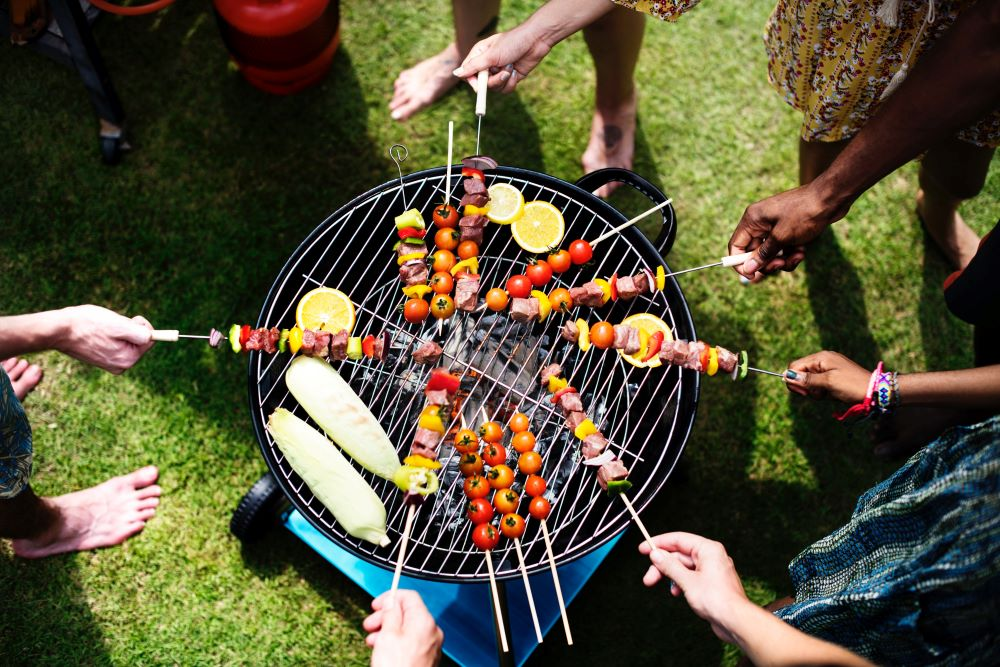 People standing around a grill cooking chicken , steak, and veggies on a stick