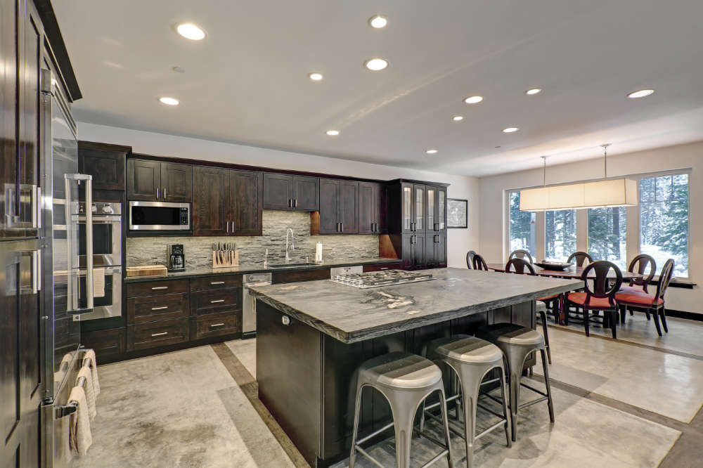 a large open kitchen with dark brown cabinets and gray backsplash and stone countertops