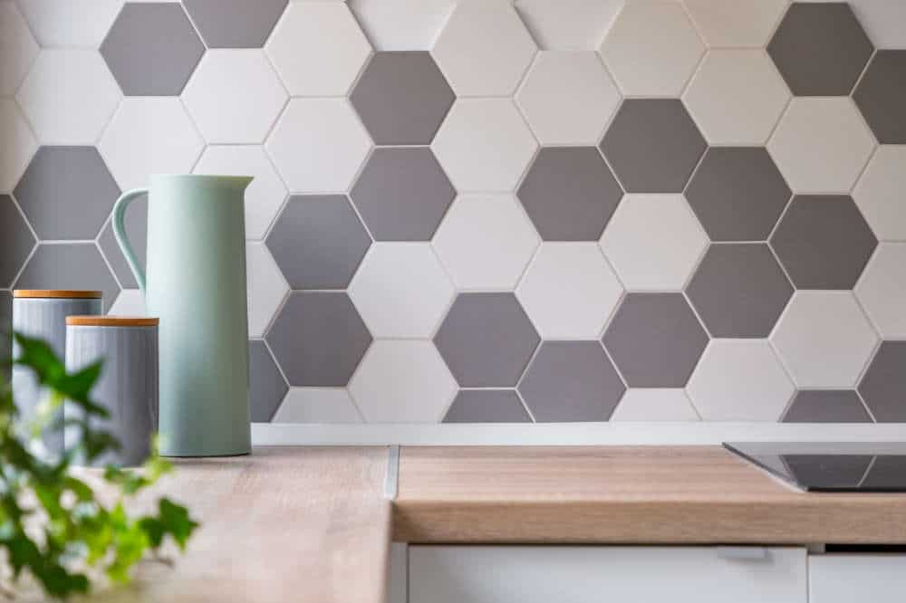 a closeup of a kitchen backsplash hexagon gray and white ceramic tiles
