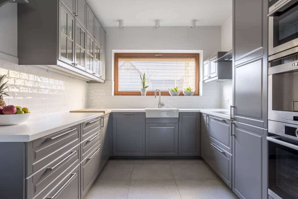 looking straight into a galley kitchen with gray kitchen cabinets and white tile