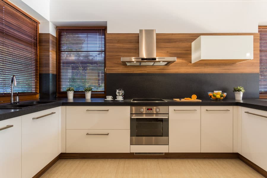 the inside of a modern kitchen with wooden blinds covering windows