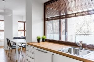 a modern kitchen at an angle looking into the window and blinds