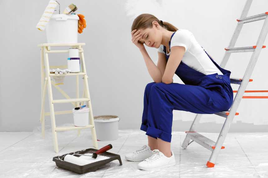 a sad woman sitting on a ladder holding her forehead for making a remodel mistake