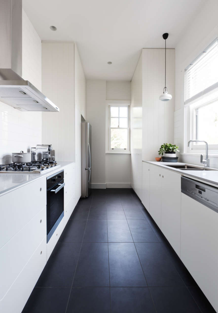 A long white galley kitchen with counters and cabinets on both sides