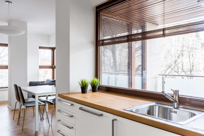 A photo capturing the long end of a small kitchen wooden countertop and white cabinet