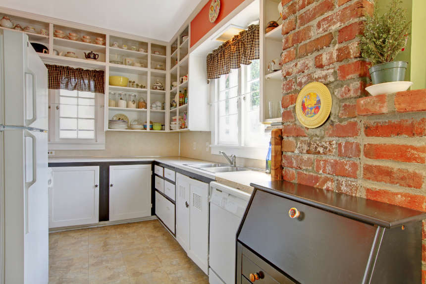 A simple white kitchen with open shelves to make it seem larger