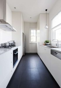 Vertical photo of a long galley style monochrome newly renovated kitchen