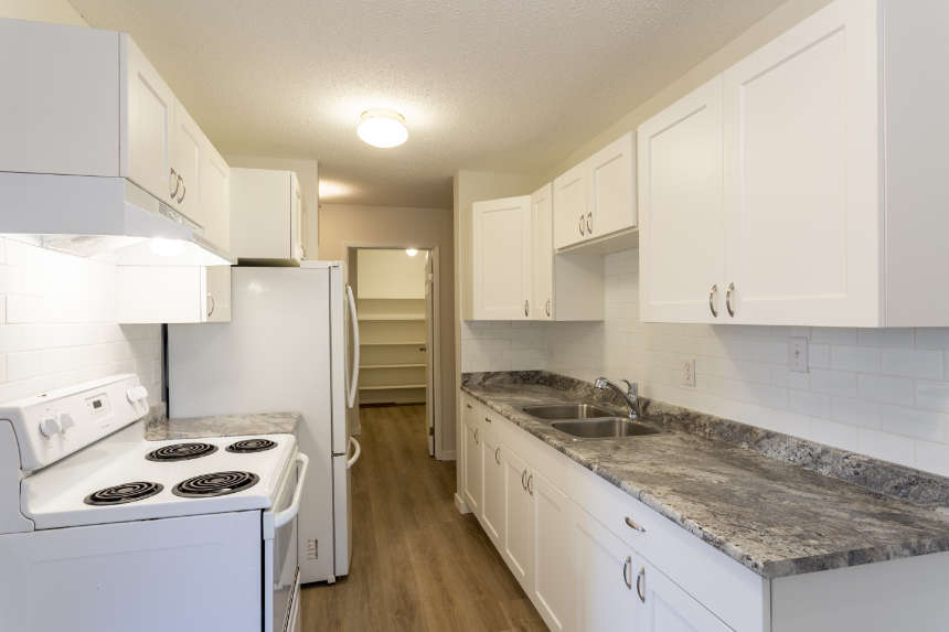 The interior of a small galley kitchen inside an empty apartment condo