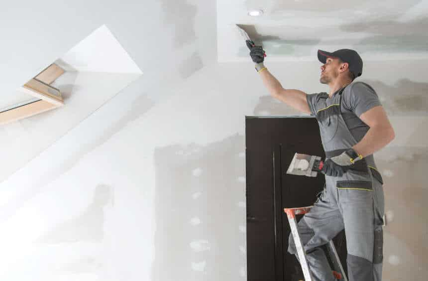 a remodeling contractor up on a ladder finishing ceiling drywall